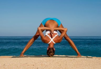 Woman in blue shorts and white top bending in yoga pose, Prasarita Padottanasana,  on beach, Hawaii