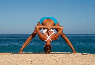 Woman in blue shorts and white top bending in yoga pose, Prasarita Padottanasana, on beach, Hawaii